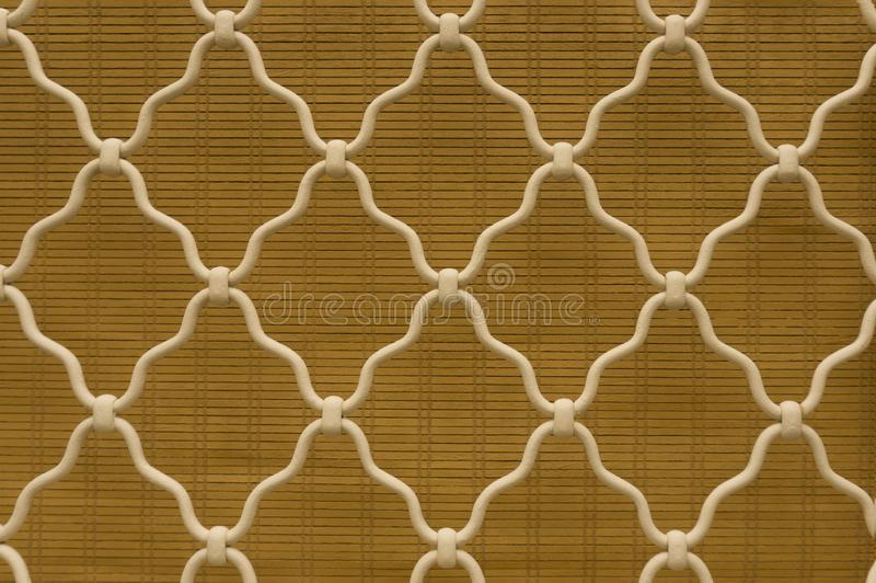 Diamond shape of white curved wrought iron steel on the lattice window, brown bamboo curtain background, vintage style lattice. Work for house decoration royalty free stock photos