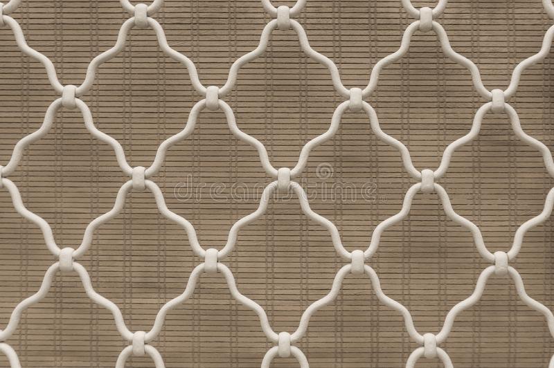 Diamond shape of white curved wrought iron steel on the lattice window, gray bamboo curtain background, vintage style lattice work. For house decoration royalty free stock image