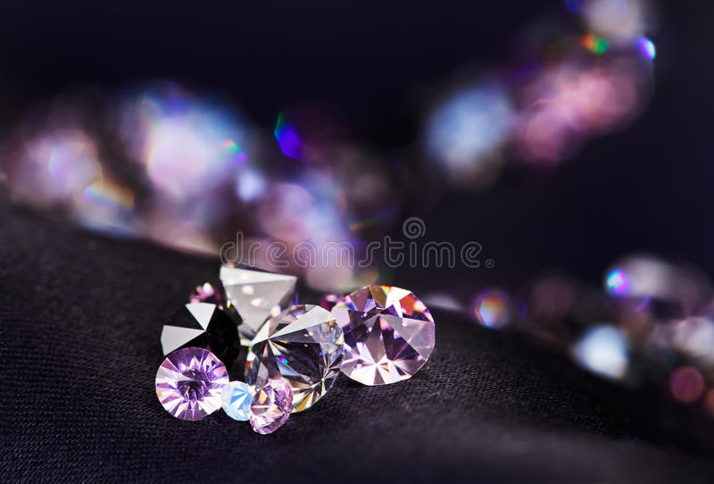 Diamond (small purple jewel) heap over black silk. Diamond (small purple jewel) stones heap over black silk cloth background stock images