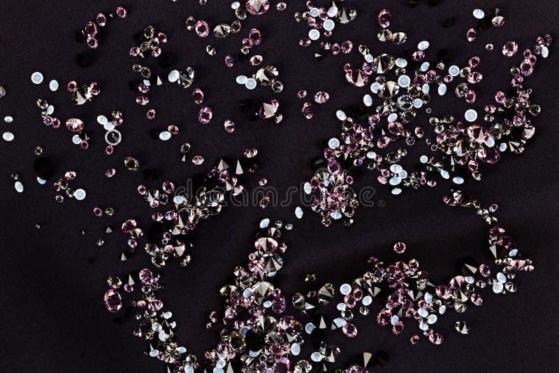 Diamond (small purple jewel) over black silk. Diamond (small purple jewel) stones heap over black silk cloth background royalty free stock image