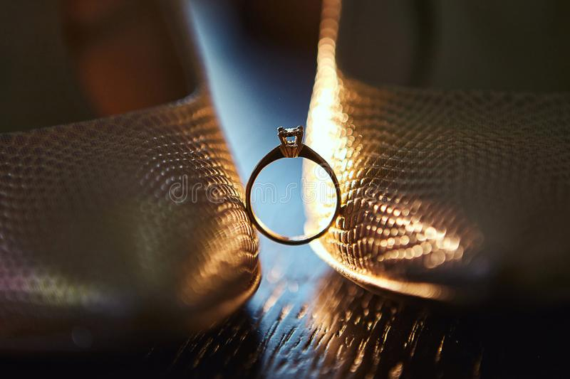 Diamond wedding ring between the shoes of the bride with splashes of perfume in the background royalty free stock photo