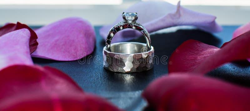 Diamond Wedding Rings a entouré par les pétales de rose rouges image libre de droits