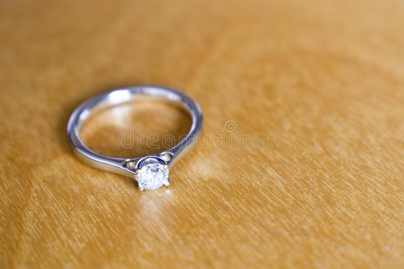 Diamond white gold engagement ring on wooden table. Closeup during bright dayligh stock photography