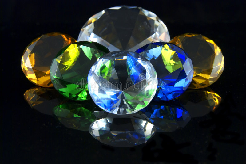 Diamonds. Attractively colored diamonds and gems on a black background stock image
