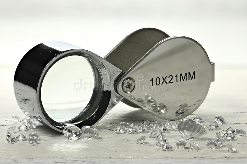 Diamonds. Brilliant cut diamonds with folding magnifier on wooden background royalty free stock photography
