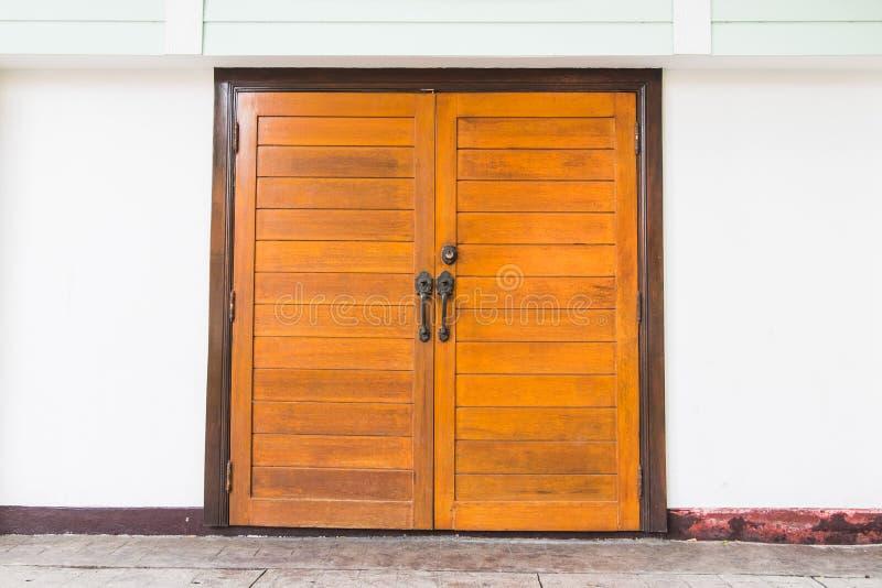 Dianteiro, claro - portas dobro de madeira velhas marrons com paredes brancas imagens de stock royalty free