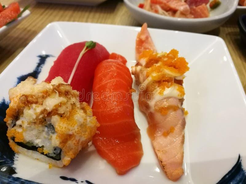 Diapositiva de color salmón fresca del sashimi el cocinar y servicio en la placa de plata con el limón Comida japonesa tradiciona imagen de archivo libre de regalías
