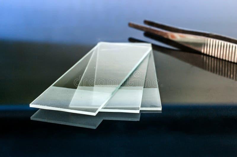 Diapositivas de cristal del microscopio que reflejan en la tabla de cristal con los alicates en el fondo fotografía de archivo libre de regalías