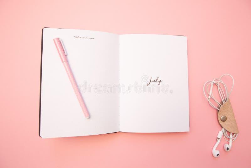 Diario abierto con una pluma rosada y auriculares en fondo de papel rosado milenario en colores pastel Concepto de aprendizaje, e fotos de archivo libres de regalías