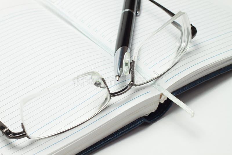 Diario abierto del asunto con la pluma y los vidrios foto de archivo libre de regalías