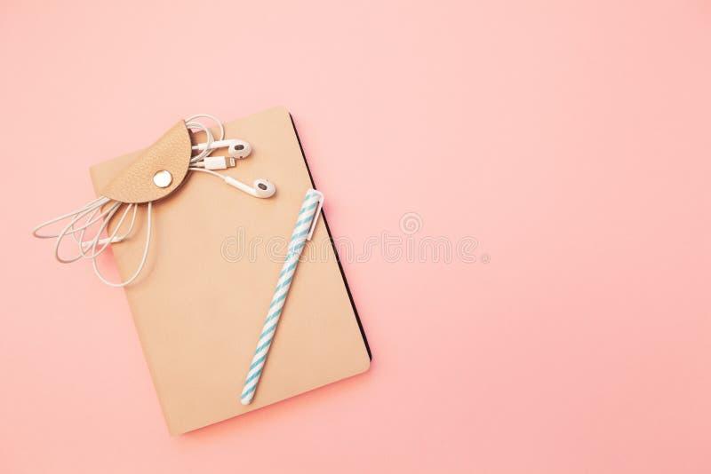 Diario beige con la pluma azul y auriculares en fondo de papel rosado milenario en colores pastel Concepto de educación, bloguean fotografía de archivo