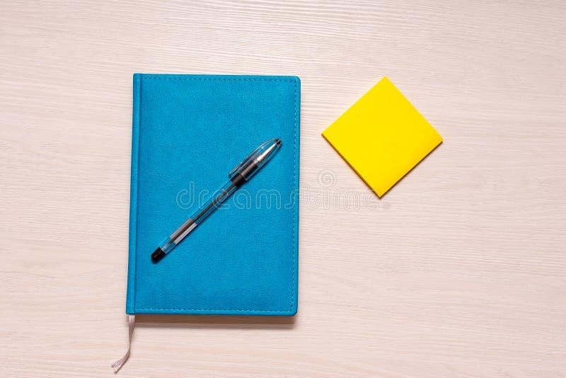 Diario chiuso di colore del turchese con una penna nera sugli autoadesivi superiori e gialli a destra, vista superiore fotografia stock libera da diritti