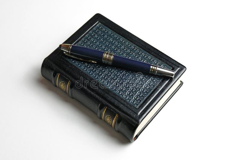 Diario de cuero azul con la pluma azul marino sobre la cubierta de libro imágenes de archivo libres de regalías