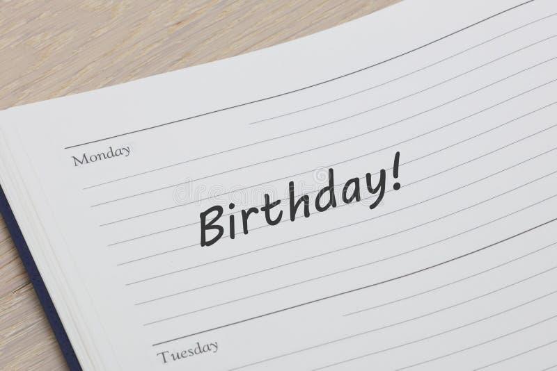 Diario del cumpleaños del recordatorio del diario en el escritorio de madera abierto para paginar mostrar la entrada del cumpleañ imágenes de archivo libres de regalías