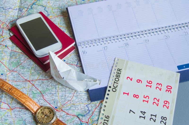 Diario e calendario con l'orologio, passaporto, carta, barca di carta, spazio della copia di concetto di viaggio immagini stock