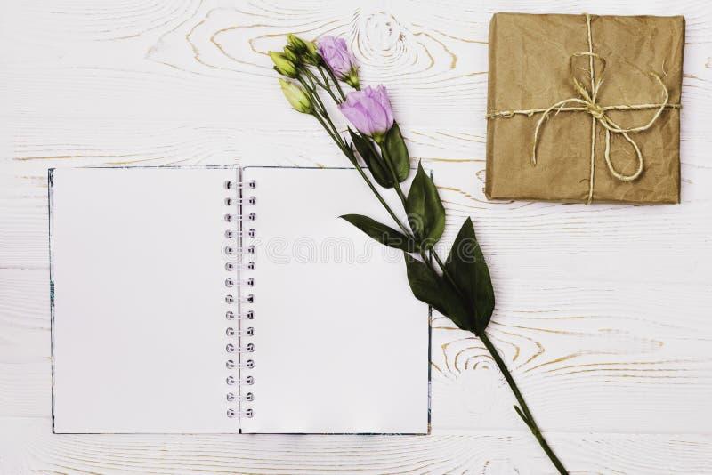 Diario en blanco vacío, flor púrpura y caja envueltos en el documento y la guita de Kraft sobre una tabla de madera lamentable bl imágenes de archivo libres de regalías