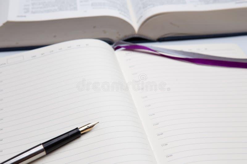 Diario o libreta y pluma vacío con el primer de oro de la semilla, libro abierto grueso en fondo fotos de archivo