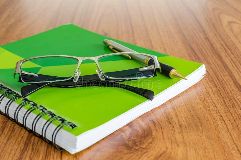 Diario verde con los vidrios y la pluma negros del oro fotos de archivo libres de regalías