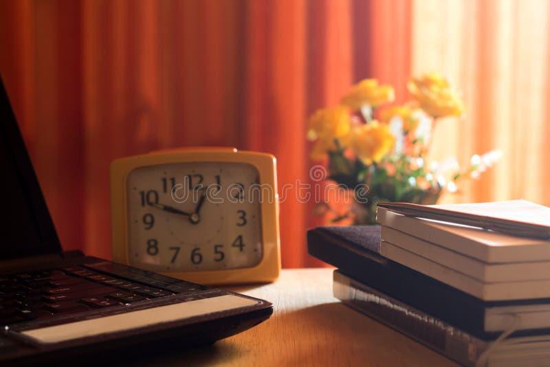 Diario y labtop para el trabajo sobre la tabla de madera con la flor y la cortina roja, cuaderno, libro, pluma, diario, reloj y s foto de archivo libre de regalías