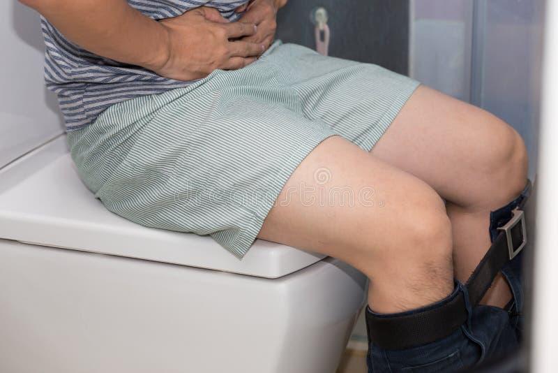 diarrea Uomo con costipazione o diarrea che si siede sulla toilette immagine stock libera da diritti