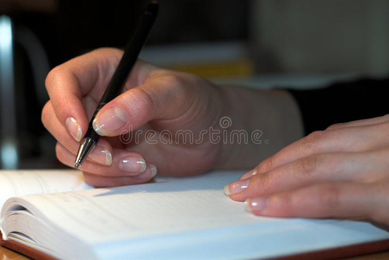 Diary. Young girl is writing notes in diary royalty free stock image