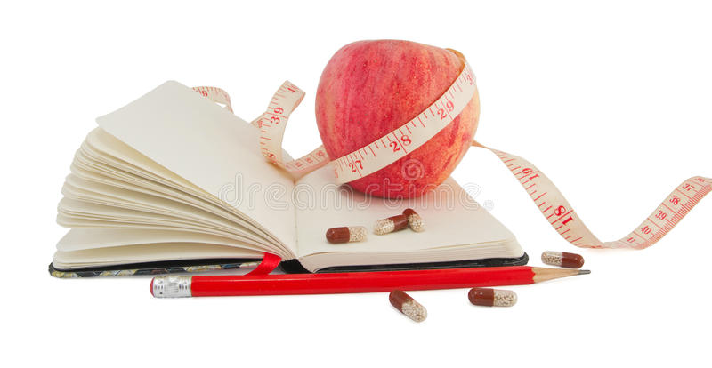 Diary with apple and pills for effective dieting stock photo