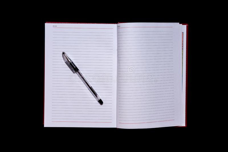 The diary with blank pages in the centre of the frame and a pen on top, a black isolated background, copy spase, mock up stock photo