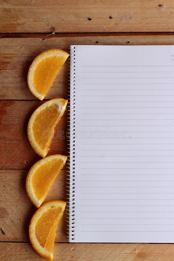 Diary book with fruit, orange slice on wooden background. Diary book with fruit, orange slice on wooden background royalty free stock photo