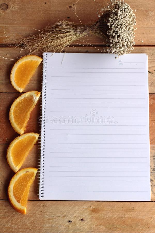 Diary book with fruit, orange slice on wooden background. Diary book with fruit, orange slice on wooden background royalty free stock images