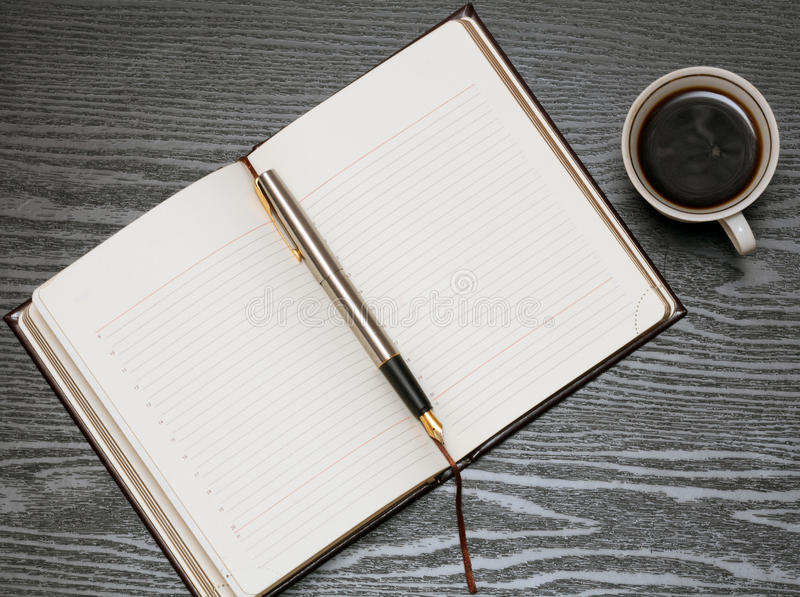 Diary book. Open diary book, pen and coffee on a black wooden table stock image