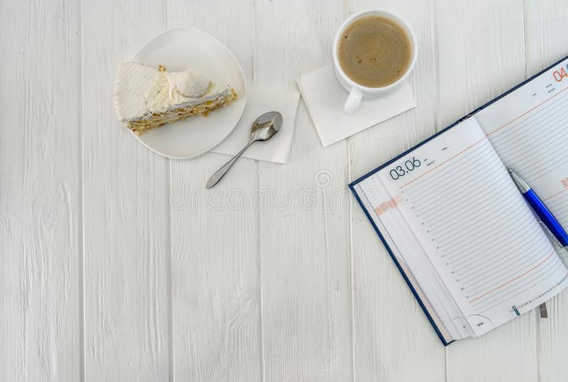 Diary with cup of coffee and piece of cake.  royalty free stock image