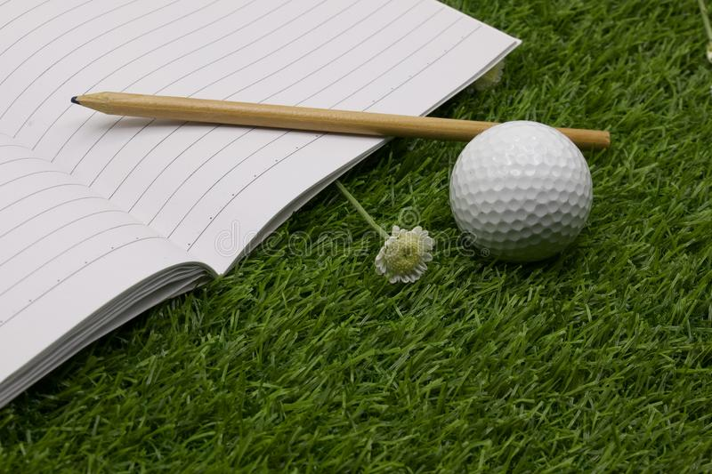 Diary of golfer with golf ball is on green grass royalty free stock images