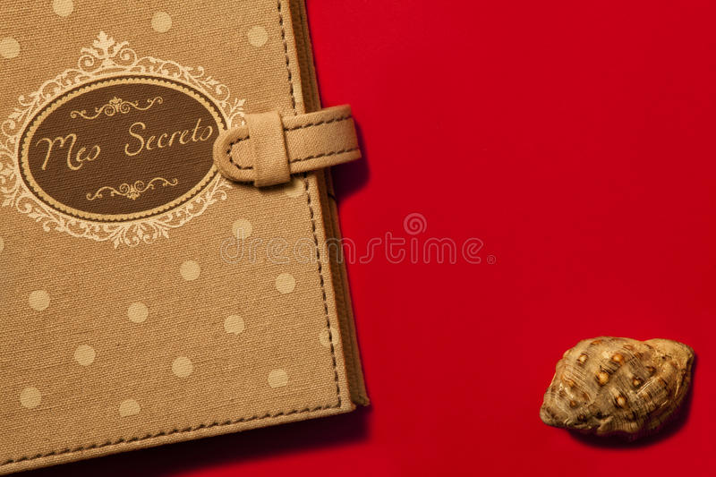 Diary my secrets French and seashell. Red background. A booklet, little black book entitled My Secrets on a red background. A seashell on the right side down stock photography