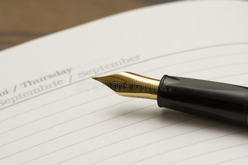 Diary and Pen. A closeup view of the golden nip of a black fountain pen on an open page of diary/organizer of a Thursday in september stock image