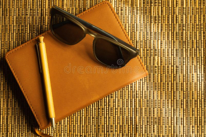 Diary and pen with sunglasses on a wooden bamboo background. notebook and pen top view royalty free stock image