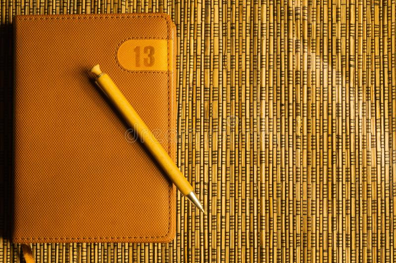Diary and pen on a wooden bamboo background. notebook and pen top view stock photos