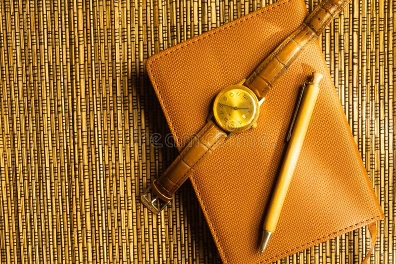 Diary and pen with wristwatch on a wooden bamboo background. notebook and pen top view stock photography