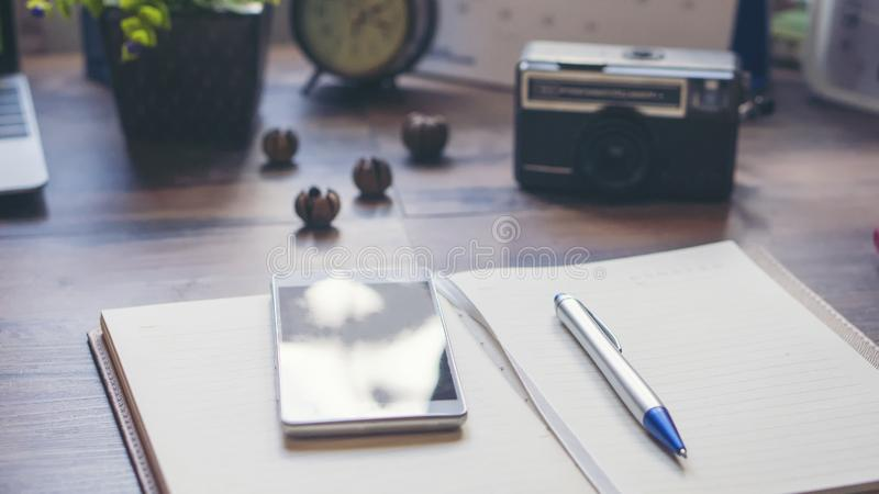 Diary and smartphone. For planning work schedules and appointments.Desktop laptop,calendar,clock,diary,book and old camera on wooden desk,Working space at home royalty free stock image