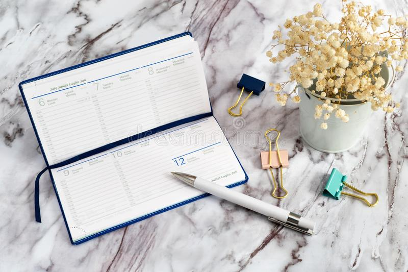 A diary with a white pen and paper clips on a marble table and white flowers. Notebook for business records for a week. A blue diary open with a white pen and stock image