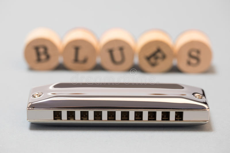 Diatonic blues harmonica. On grey background with word blues stock images