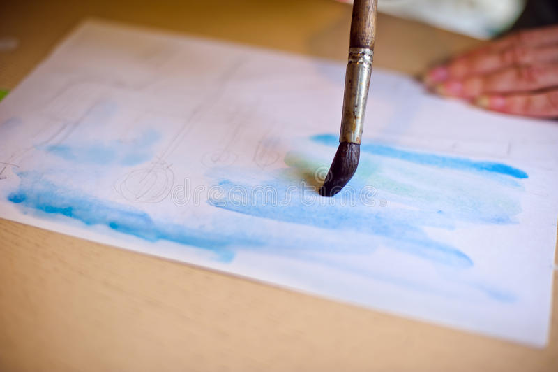 Dibuja el cepillo en el azul del papel fotos de archivo