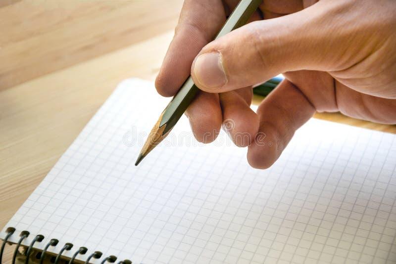Dibuje a lápiz en la mano masculina y la hoja clara del cuaderno fotos de archivo