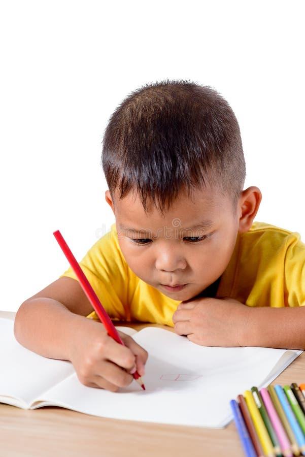 Dibujo alegre lindo del niño usando el lápiz del color mientras que se sienta en la tabla aislada en el fondo blanco foto de archivo libre de regalías