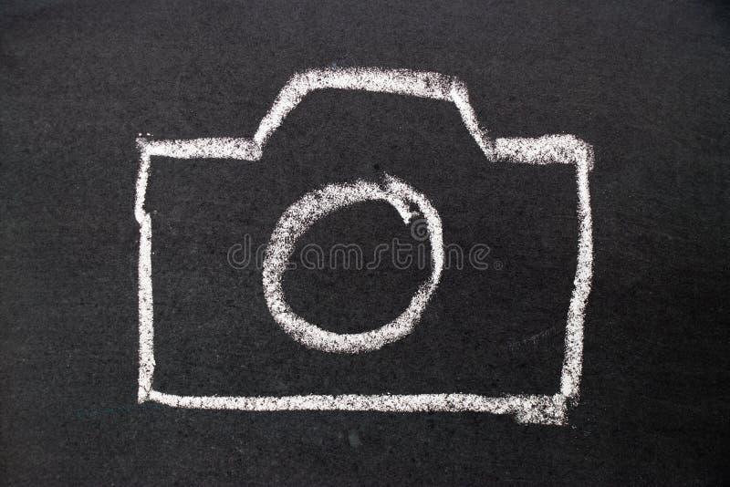 Dibujo blanco de la mano de la tiza como icono de la cámara en tablero negro fotografía de archivo libre de regalías