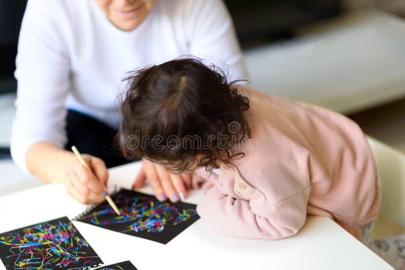 Dibujo de la abuela y de la nieta así como el palillo en el papel de pintura del rasguño mágico en casa o en clase imagen de archivo libre de regalías