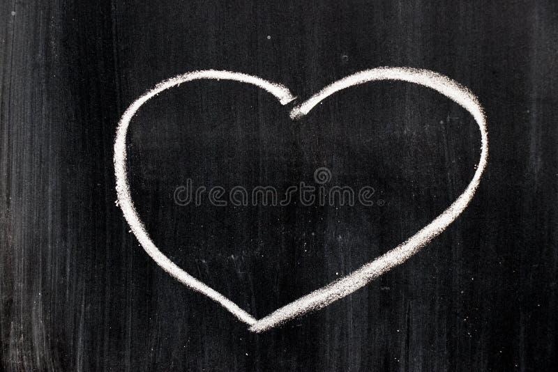 Dibujo de la mano de la tiza como forma del corazón en tablero negro fotos de archivo