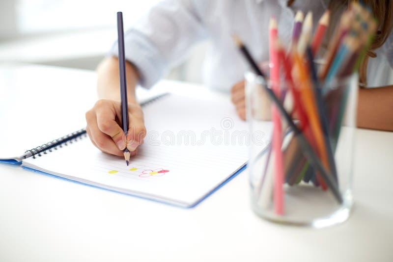 Dibujo de la muchacha con la pluma del lápiz del color en cuaderno fotos de archivo