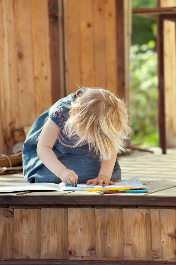 Dibujo de la niña con los lápices coloreados en una madera de la casa de campo foto de archivo libre de regalías