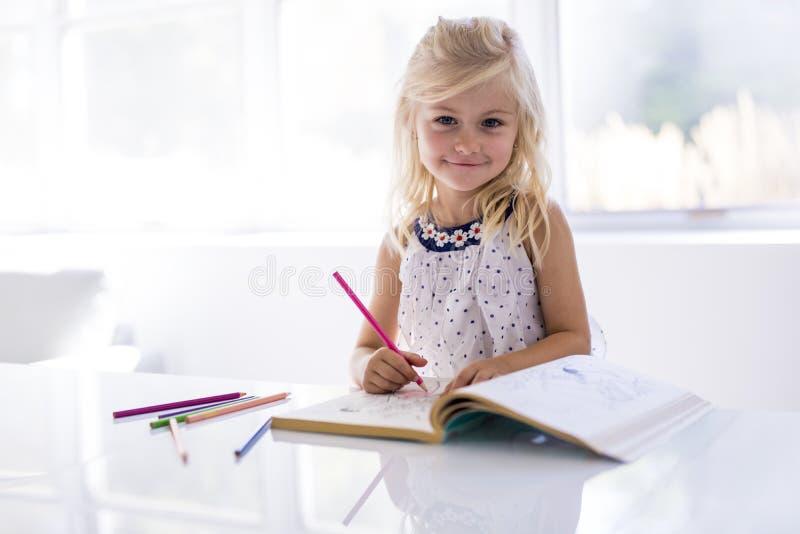 Dibujo de la niña en la tabla de cocina fotos de archivo
