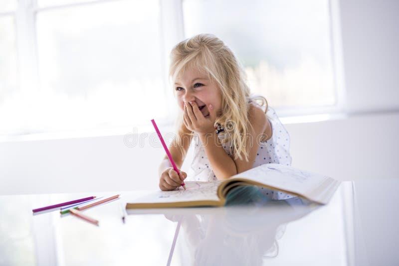 Dibujo de la niña en la tabla de cocina foto de archivo